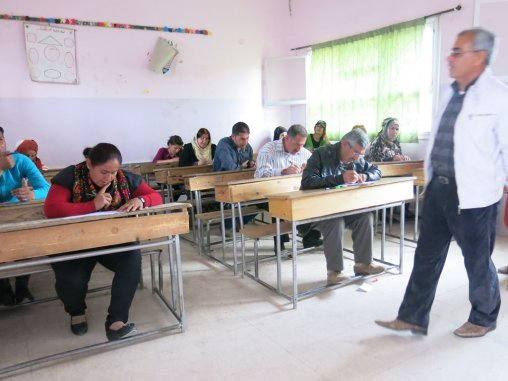 Des adultes suivent des cours de langue kurde (interdits avant la révolution). © Firat News